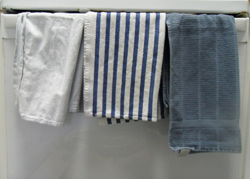 Fresh kitchen towels hanging on the oven handle